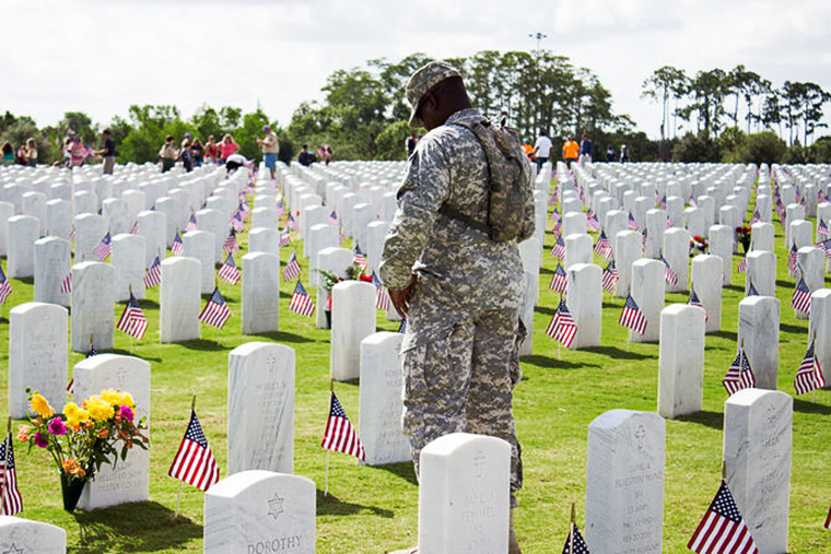 Memoria Day image of U.S. soldier at cemetery pay respects
